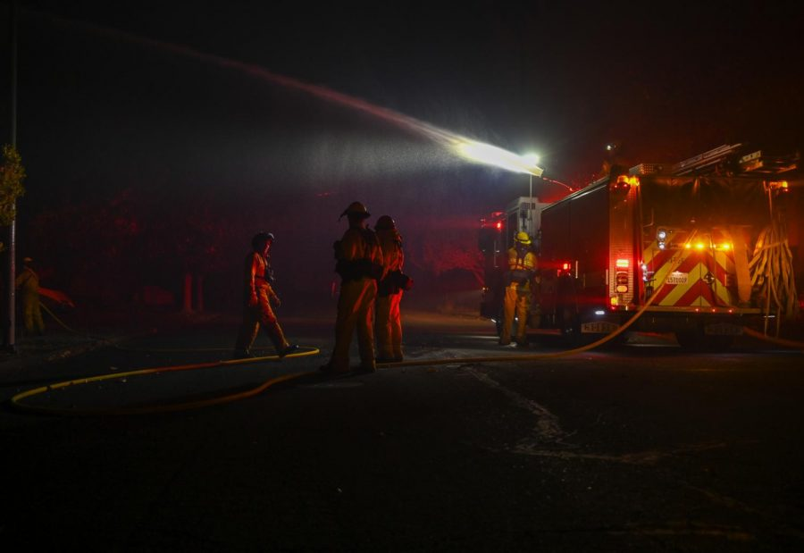 Santa Rosa Fire Department firefighters work to extinguish a fire started by embers in the front yard of 5229 Piedmont Court in East Santa Rosa, California early Monday morning. (James Wyatt / Xpress Media)