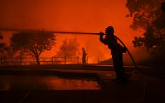Firefighters spray water on a house located on Vaughn st in East Santa Rosa, California early Monday morning. (James Wyatt / Xpress Media)