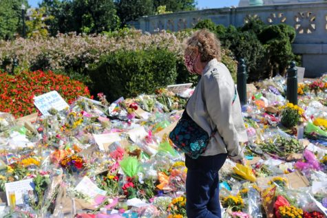 An older woman looks toward the display of gifts and goods in memory of Ginsburg. (Olivia Wynkoop / Xpress Media)