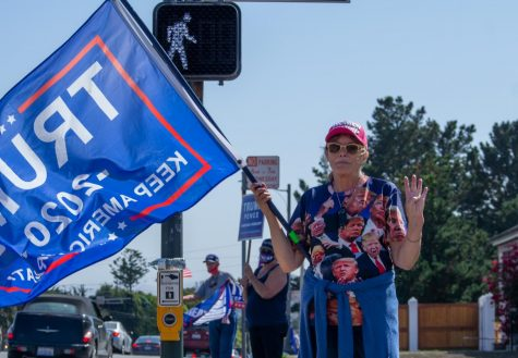 "Trump supporter Nancy A. poses with four fingers up representing ""four more years"", a common Trump slogan, on Sunday Sep. 27, 2020. (Jess Magill / Xpress Media)"