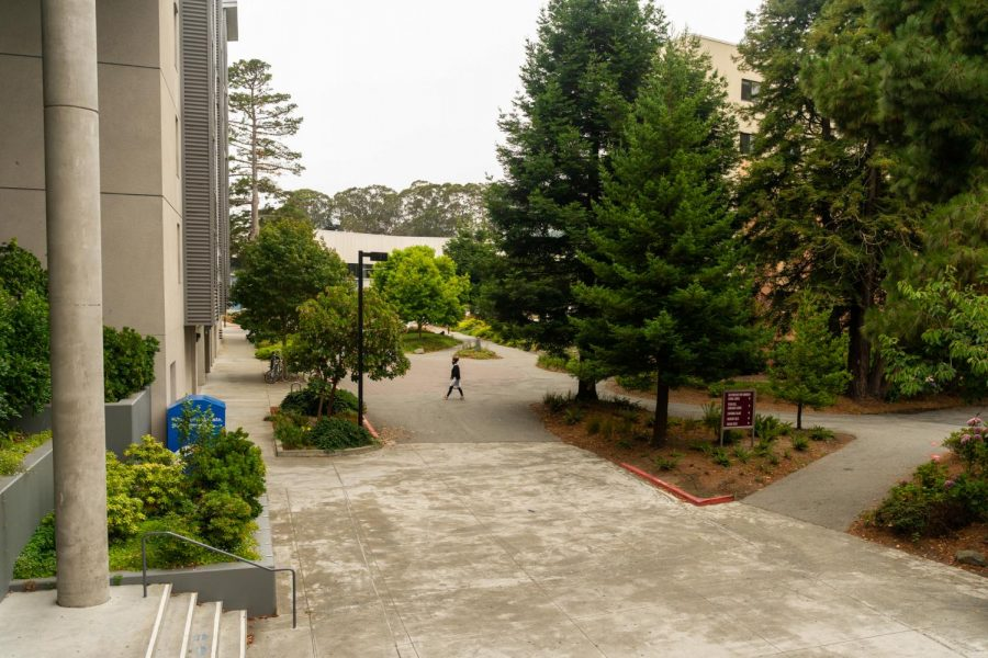 A woman walks towards a residential building at the Village at Centennial Square during the first week of Fall classes on August 27. Since the university has transitioned to a primarily online learning format, the campus has low foot traffic during usual peak hours. (Jun Ueda / Golden Gate Xpress)