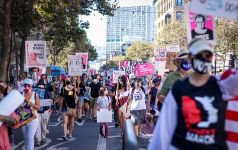 People march down the Market Street holding various signs related to women's rights, honoring the late Justice Ruth Bader Ginsberg, voting President Trump out, and urging people to go out and vote, during Women's March in San Francisco on Oct. 17, 2020. (Harika Maddala / Golden Gate Xpress)