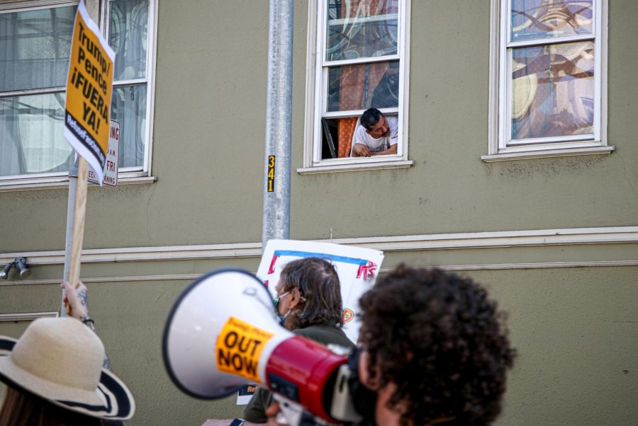 A resident leans out from his window to look at the protesters marchingon the 18th St. in San Francisco on Oct. 24, 2020. (Harika Maddala/ Golden Gate Xpress)