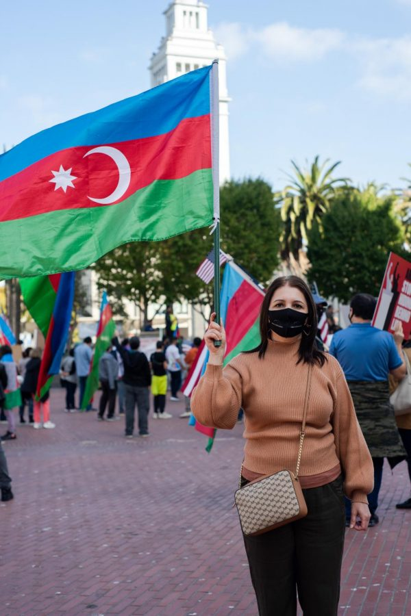 Nikka Mammad waves an Azerbaijan flag at a Nagorno-Karabakh protest in the Embarcadero of San Francisco near the Ferry Building on Saturday, Oct 24. Mammad and a hundred others gathered to demand justice for the Azerbaijanis civilians who were affected by a ballistic missile strike from the Armenian military that killed 13 and injured 50 on Oct. 17. (Jun Ueda / Golden Gate Xpress)