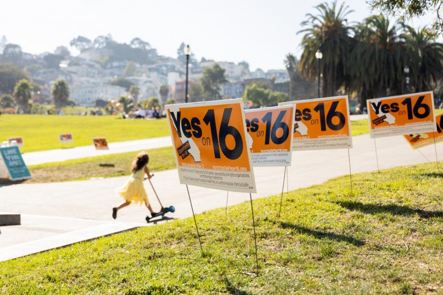 A girl passes by several Proposition 16 signs left after a rally held earlier in the day in Mission Dolores Park on Saturday, Oct. 31. Proposition 16 would restore affirmative action at public institutions in the state of California. (Jun Ueda/Golden Gate Xpress)