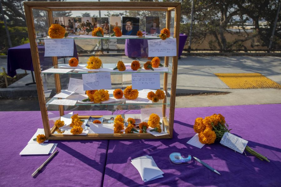 A table with ofrendas set up with pens, paper, tape and marigold flowers at the Outer Sunset Farmers Market to encourage the community to write messages to loved ones who died for Día de los Muertos on Nov. 1, 2020. (Emily Curiel / Golden Gate Xpress)