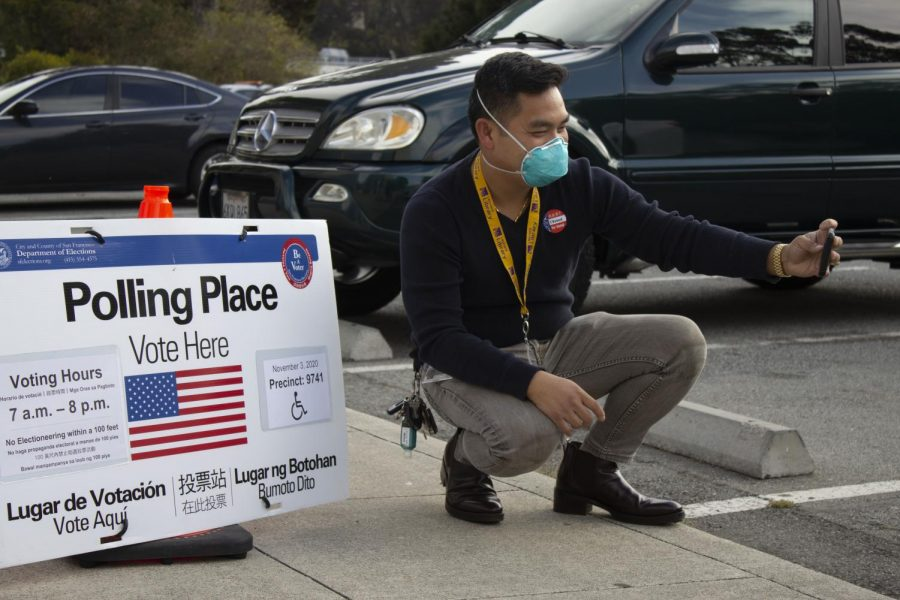 Kim Wong a system administrator at SF State takes a picture of himself with the polling place sign at SF State in San Francisco, Calif., on Tuesday, November 03, 2020. Katherine Burgos/Golden Gate Xpress)