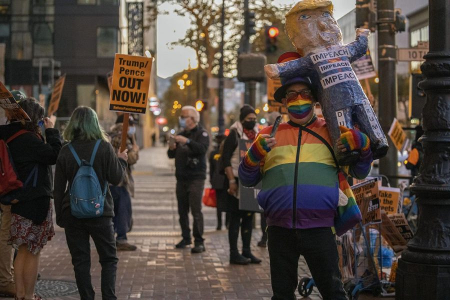Michael Petrelis holds a taped-up President Trump piñata as he stands along side other demonstrators at Twitter Headquarters in Downtown San Francisco as they rally for the protection of the election's results and integrity on Nov. 4, 2020. (Emily Curiel / Golden Gate Xpress)