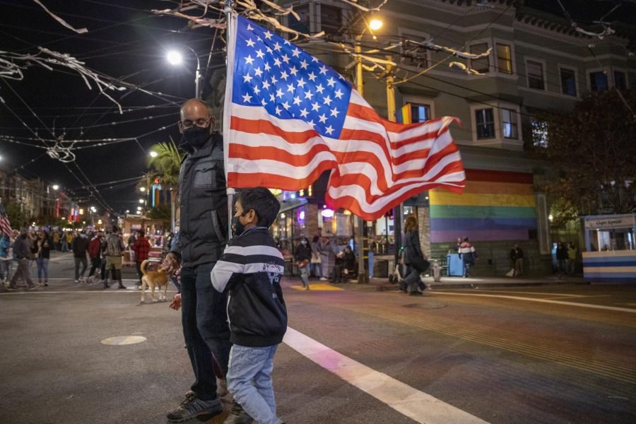 Shiv Singh dances on the corner of 18th Street and Castro Street holding a big American flag while being supervised by his parents to celebrate JoeBiden and KamalaHarris' election victory on Nov. 7, 2020. (Emily Curiel / Golden Gate Xpress)
