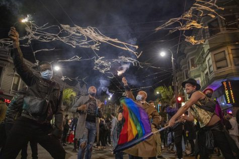 (Left to right) Kai Reynolds, Maurice Nichols and Kohei Shimamoto wave sparkers in the air on Castro Street to celebrate Joe Biden and Kamala Harris' election victory on Nov. 7, 2020. (Emily Curiel / Golden Gate Xpress)