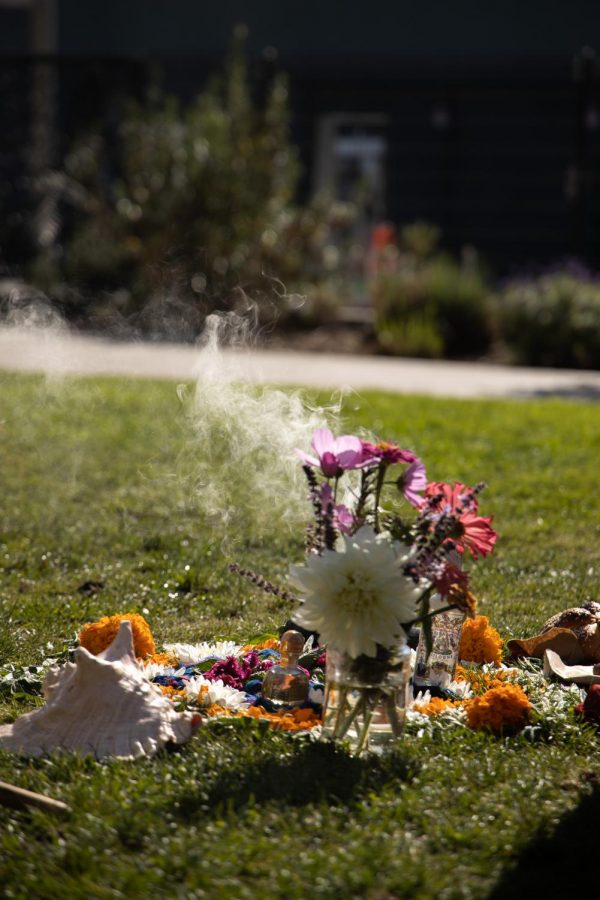 Flower petals, a conch, bread, and a bottle of Florida Water surround an incense burner set up next to an Aztec Drum, at In Chan Kaajal Park in the Mission District on Saturday, Oct. 31. (Jun Ueda / Golden Gate Xpress)