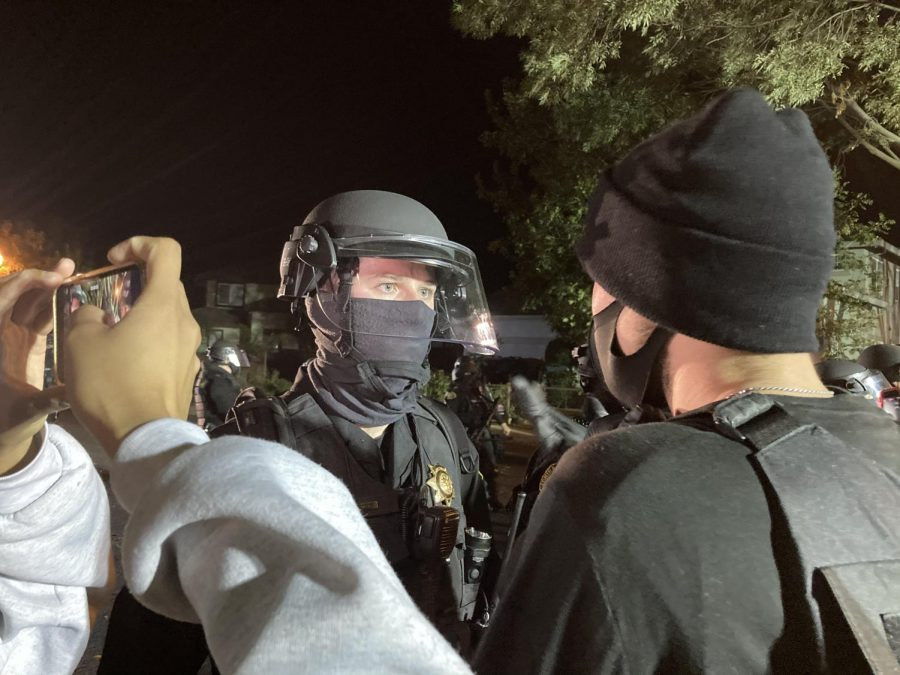Michael, an active protester in events across the Bay Area, questions a BPD officer helping hold a perimeter in front of Eric Harvey's home as to why BPD is protecting Harvey, rather than the community in Brentwood, Calif., on Nov. 6, 2020. (Joel Umanzor, Jr. / Golden Gate Xpress)