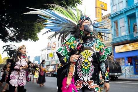 An Aztec dancer looks above the trees on 24th street, during a walk towards 24th and Folsom st. in San Francisco on Sunday, Nov. 1, 2020. (Sebastian Mino-Bucheli / Golden Gate Xpress)