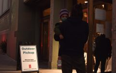 "The Berkeley Public Library hands out ""on-hold"" books to guests through a plastic shield in compliance with new restrictions implemented this week on Kettner St. On Dec.8, 2020 (Leila Figueroa / Golden Gate Xpress)"