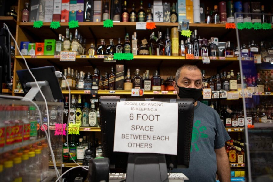 Sam Kaleh, owner of Lucca Food Deli & Wine Shop, waits behind the register for customers in San Francisco on Aug. 30, 2020. (Sean Reyes / Golden Gate Xpress)