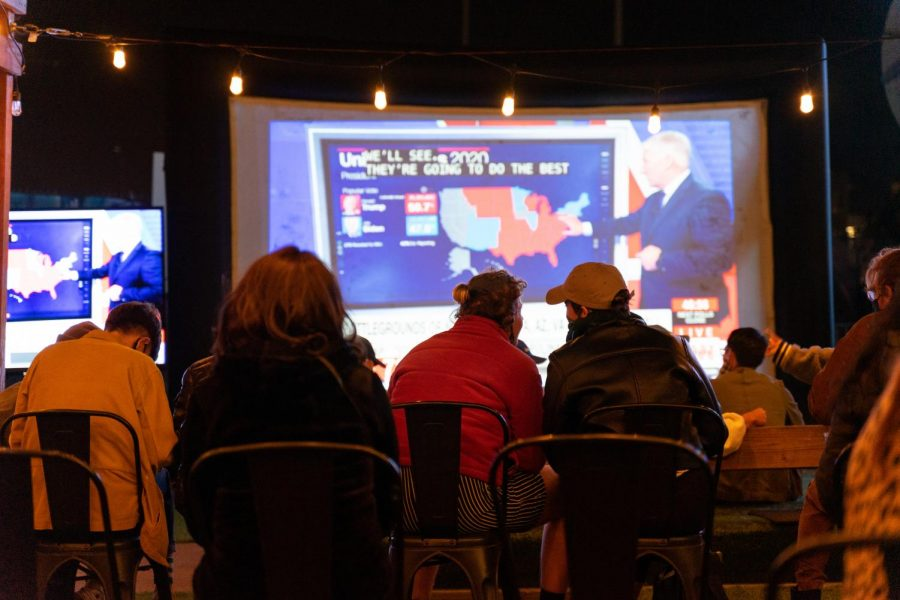 Visitors of 7th West in Oakland, Calif., watch the election night coverage in an outdoor seating area with multiple large projectors on Nov. 3, 2020. (Jun Ueda/Golden Gate Xpress)