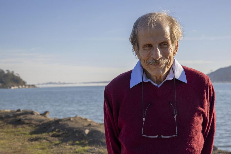 Author, professor and the host of KQED's 'Forum' Michael Krasny smiles and looks away during his walk on a trail overlooking the bay water at Blackie's Pasture in Tiburon on Dec. 6, 2020. (Emily Curiel / Golden Gate Xpress)