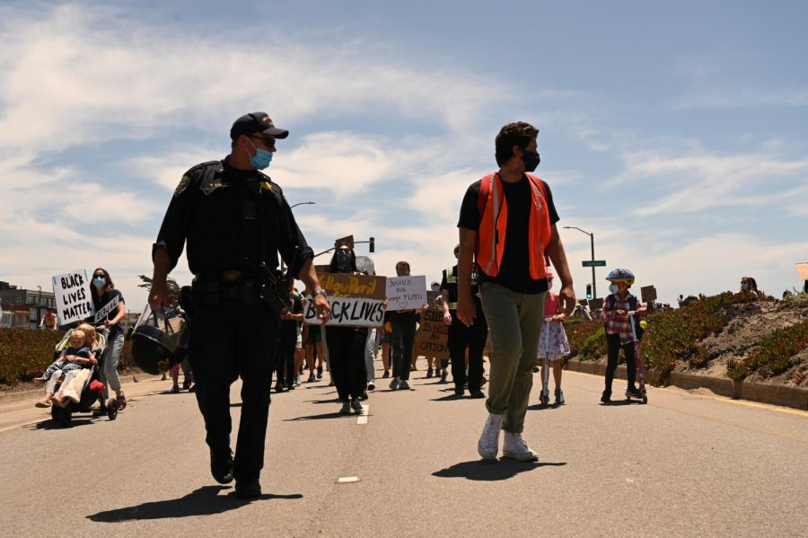 A protester walks with a San Francisco Police officer during a Black Lives Matter protest that went from Sloat Boulevard to Lincoln Way via the Great Highway in San Francisco, on June 2, 2020. The protest was in response to the death of George Floyd, a detained and handcuffed black man in police custody in Minneapolis. (James Wyatt / Golden Gate Xpress)