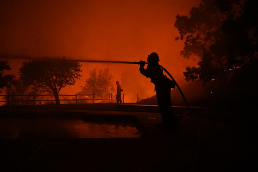 Firefighters spray water on a house located on Vaughn st in East Santa Rosa, California early Monday morning. (James Wyatt / Golden Gate Xpress)