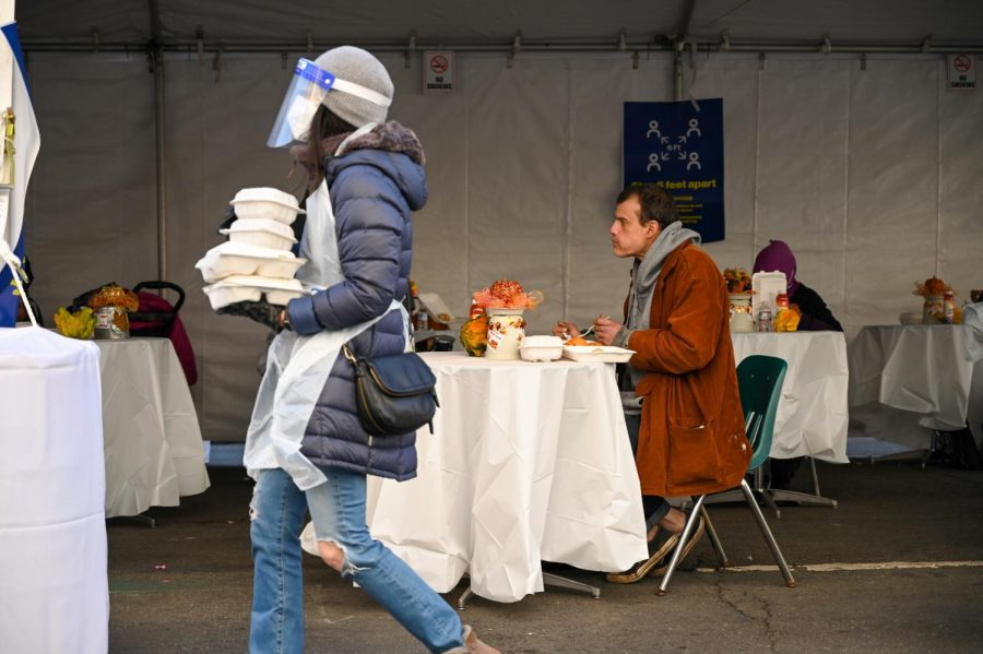 A client of GLIDE eats while a volunteer carries empty food containers to be thrown away meal on Nov.26, 2020 in San Francisco. (James Wyatt / Golden Gate Xpress)
