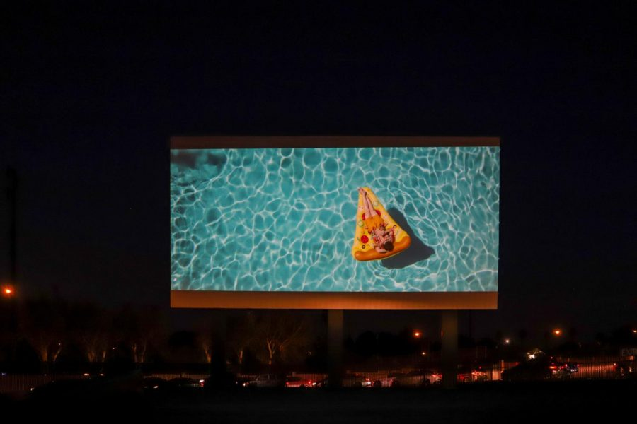 """Cars line up to purchase tickets at the Van Buren Drive-in while """"Palm Springs"""" plays on one of the many projection screens. (Camille Cohen / Golden Gate Xpress)"""