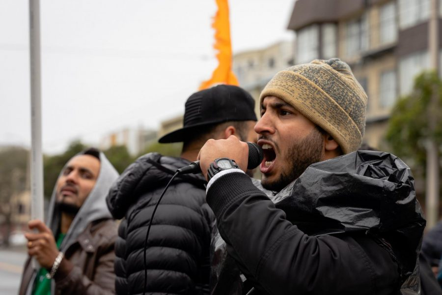 A man passionately chants into a microphone in unison with several dozen protesters outside of the Consulate General of India. (Jun Ueda / Golden Gate Xpress)