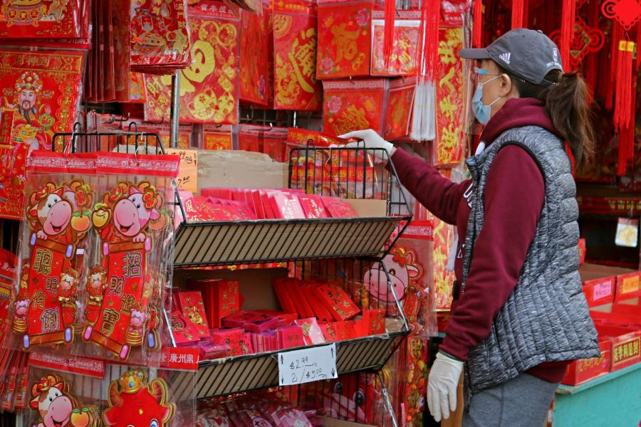 A woman shops in a stall of red and gold decoration items in Oakland, CA., on February 8, 2021, in preparation for the Lunar New Year. (Sabita Shrestha /   Golden Gate Xpress)
