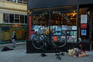 A man plays an accordion next to City Lights Books on Tuesday, February 23, 2021 in San Francisco. Flowers and candles are left in front to honor the Lawrence Ferlinghetti, who died on Monday evening at the age of 101. (Cameron Lee / Golden Gate Xpress)