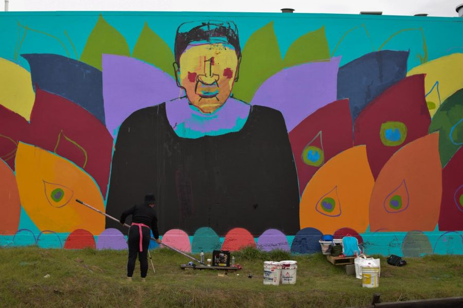 Christina Xu, a full-time artist, paints a tribute mural to Ruth Bader Ginsburg on Ninth Avenue and E 10th St. in Oakland on February 21, 2021. Xu was commissioned to paint by Paint the Void, an organization that coordinates with artists to paint murals on boarded up businesses due to COVID-19. (Leila Figueroa / Golden Gate Xpress)