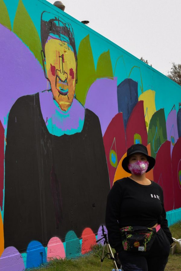Christina Xu, standing in front of her mural in Oakland, is one of many artists working with Paint the Void, an organization that uses grants and local donations to support artists with supplies and blank canvases. (Leila Figueroa / Golden Gate Xpress)