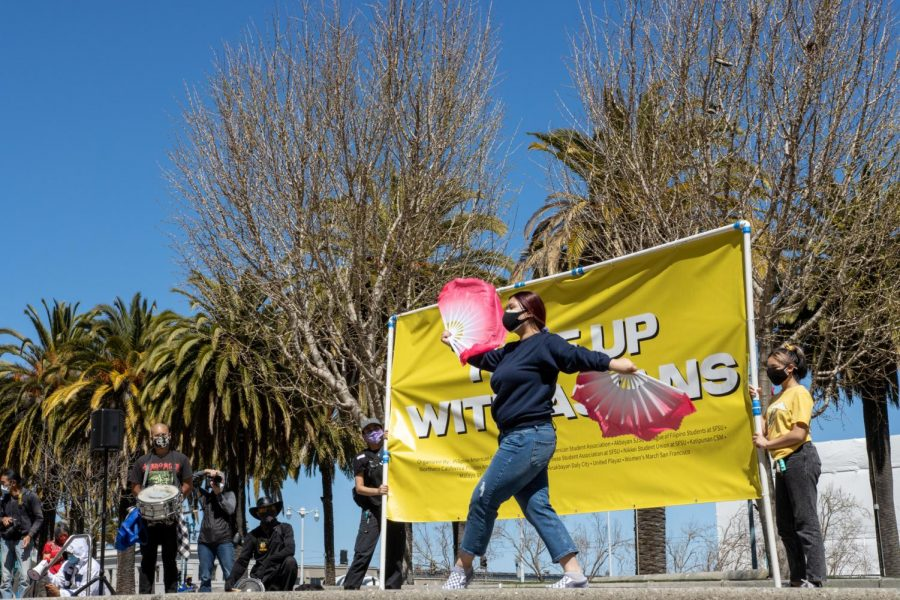 A performer dances at the Rise Up With Asians rally in the Financial District. (Amalia Diaz / Golden Gate Xpress)