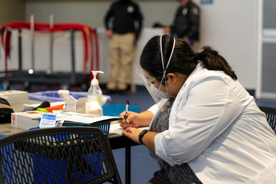 A Safeway Pharmacy employee fills out a COVID-19 vaccine passport in the Mashouf Wellness Center on Feb. 3. According to the CSU, all students and faculty who will be on campus for in-person learning during the fall semester must be vaccinated. (Jun Ueda / Golden Gate Xpress)