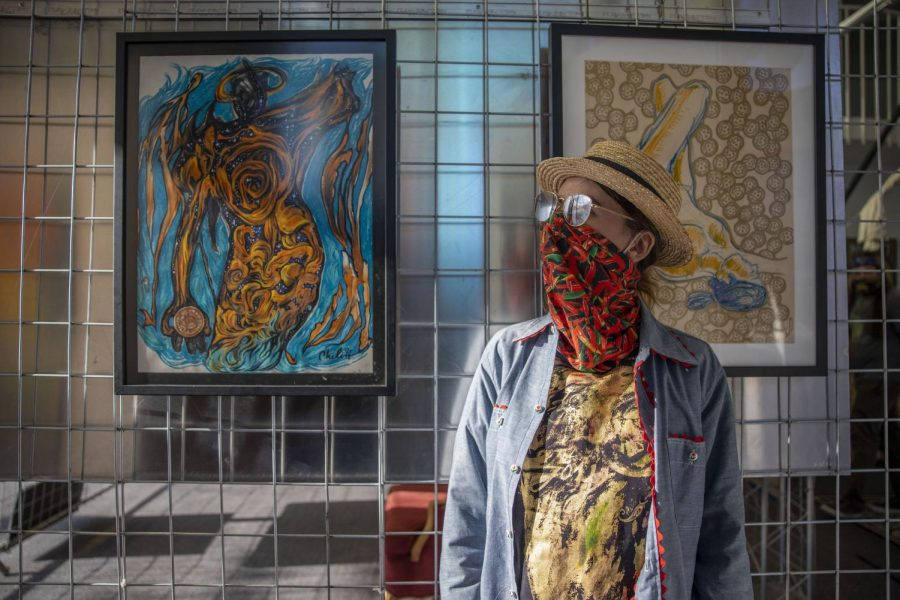 AnnaChili, a San Francisco artist, displays her paintings on a metal rack for people to see at Local Maker Mart Gallery. (Emily Curiel / Golden Gate Xpress)