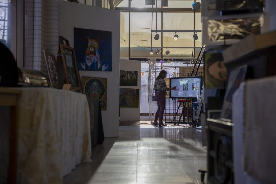 An art enthusiast scrolls through a touchscreen monitor to view local artists whose work has been converted into NFTs at Local Maker Mart Gallery on March 25. The gallery was presented by Recreation Sound Systems. (Emily Curiel / Golden Gate Xpress)