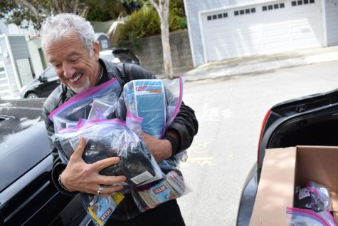 Founder of Blanket The Homeless, Ken Newman, loads his car with kits for people experiencing homelessness in San Francisco. Kits are filled with items like Cliff bars, socks, silver thermal blankets, masks, and a waterproof resource guide. (Lucky Whitburn-Thomas / Golden Gate Xpress)