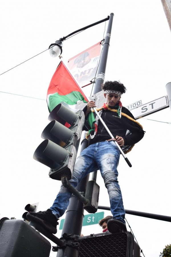A demonstrator waves a Palestinian flag atop a streetlight at the All out for Palestine rally in the Mission District on May 15. (Lucky Whitburn-Thomas / Golden Gate Xpress)