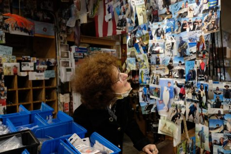 Stephanie Ernst Scott recounts one of the hundreds of stories behind the photos that line the entryway into Gus' Discount Tackle. Customers and friends have built up the shrine-like collection over decades. (Avery Wilcox / Golden Gate Xpress)