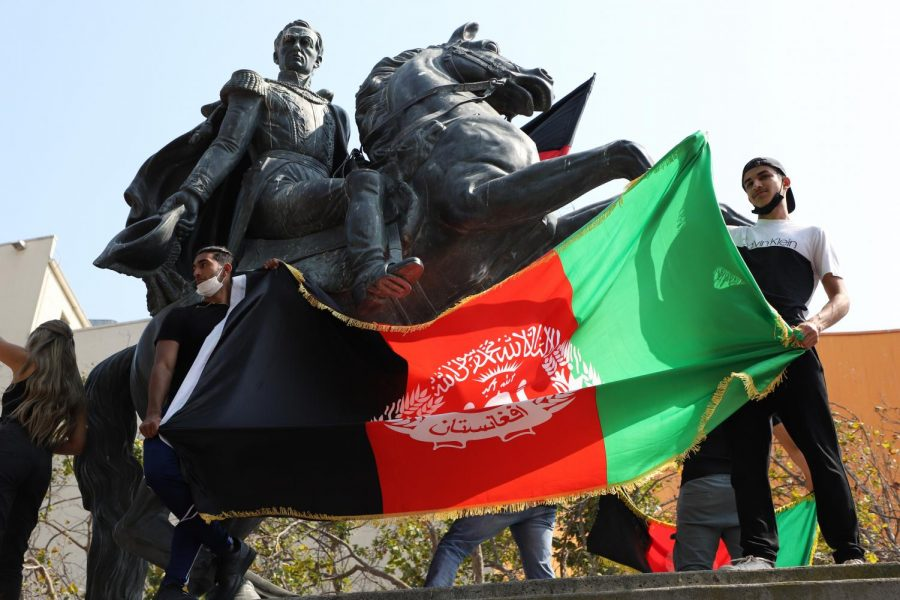 Protesters stand atop a statue while waving the Afghanistan flag at United Nations Plaza, on Aug. 28, 2021. (Amaya Edwards / Golden Gate Xpress)