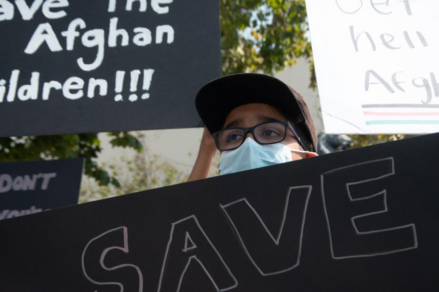 Alex Johnston, 12, holds a sign that reads, 'Save Afghanistan,' at a protest the United Afghan Association organized in the United Nations Plaza on Aug. 28, 2021. (Morgan Ellis / Golden Gate Xpress)