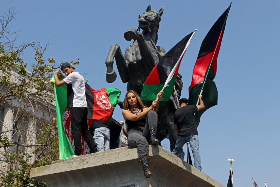 'Protest to Save Afghanistan' attendees wave flags from the statue in United Nations Plaza on Aug 28, 2021. (Sabita Shrestha/ Golden Gate Xpress)