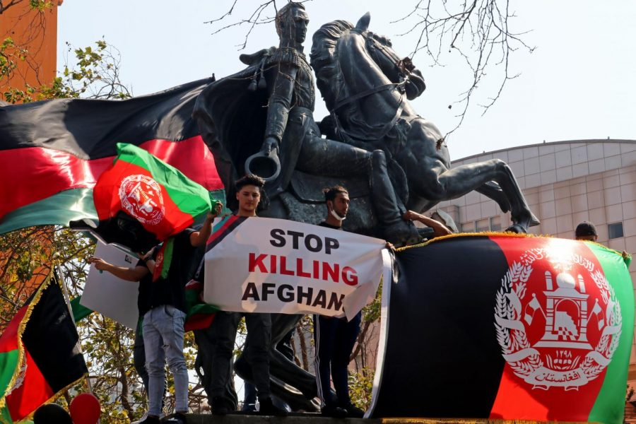 Participants at the 'Protest to Save Afghanistan' hold flags and signs in front of the statue in United Nations Plaza on Aug. 28, 2021. (Sabita Shrestha/ Golden Gate Xpress)