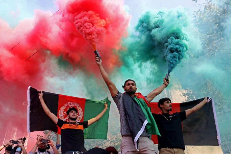 A demonstrator diffuses two colored smoke grenades, which represent the Afghanistan flag, and two participants hold the flag to the crowd on Market Street during a peaceful protest on Aug. 28, 2021. (Sabita Shrestha/ Golden Gate Xpress)