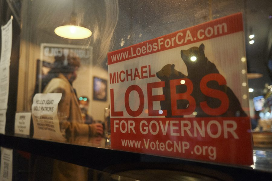 A flyer for CNP recall candidate Michael Loebs sits next to a half empty wine glass at Liquid Gold on Sept. 24, 2021. Loebs joked that the flyer could become collector's memorabilia. (Cameron Lee/Golden Gate Xpress)