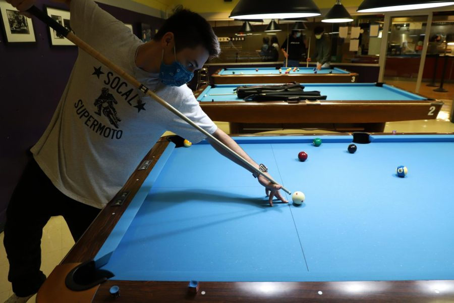 Justin Baskin, 20, takes aim at a pool ball during a game at Rack-N-Cue on Aug. 25, 2021. Baskin seemed excited for the opening, mentioning that he plays on a team that competes against other schools. (Photo by Amaya Edwards/Golden Gate Xpress)