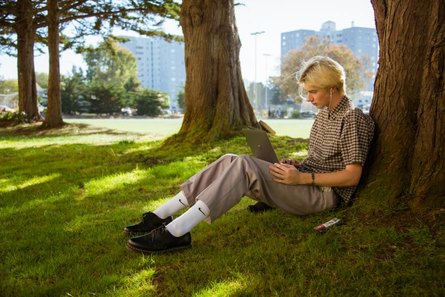 Grant Hans makes music in the shade to escape the heat in the SF State West Campus Green on Sept., 20, 2021. (Garrett Isley/Golden Gate Xpress)
