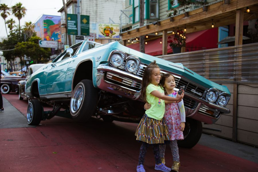 Two girls take a selfie in front of a lowrider at the 40th Anniversary Lowrider Cruise in San Francisco on Sept. 18, 2021. (Garrett Isley/Golden Gate Xpress)