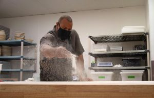 Azikiwee Anderson, founder of RizeUp Sourdough, sprinkles flour all over his workspace before he starts working with and shaping his dough in his North Beach baking space on Sept. 2, 2021. Each loaf is sized to be small enough to enjoy all at once if desired, but large enough to feel substantial and shareable. (Morgan Ellis/Golden Gate Xpress)