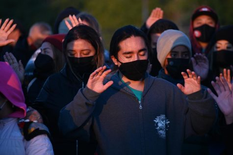 A man raises his hands with others in prayer as the sun rises on Alcatraz Island on Oct. 11, 2021. The prayer was motivated to help bring in healing attributes to those within the gathering, as they spent the early morning reflecting on Indigenous history. (Samantha Laurey / Golden Gate Xpress)